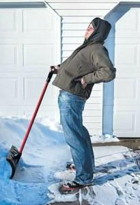 Man displaying back pain while shoveling snow from driveway