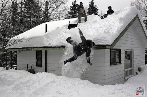 A man falling from roof while attempting to remove snow with a shovel.